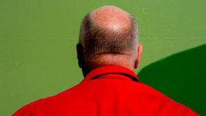 A man wearing a red jacket faces away from the camera in front of a green wall.